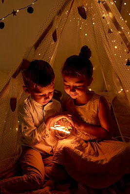 Brother and sister sitting in room while holding christmas light - p300m2220929 by Gala Martínez López