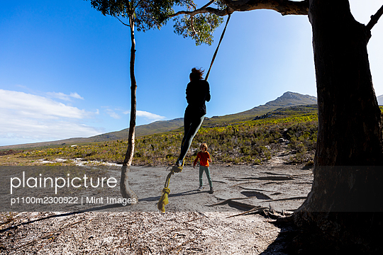 Teenage girl and younger brother using rope swing on a hiking trail - p1100m2300922 by Mint Images