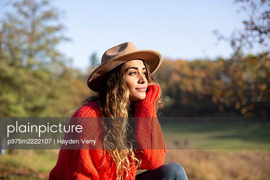 Junge Frau mit Hut tagträumend im Sonnenschein - p975m2222107 von Hayden Verry