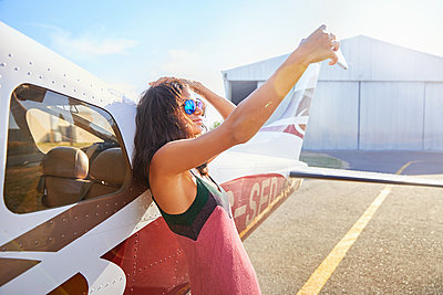Confident young woman taking selfie with camera phone at small airplane on sunny tarmac - p1023m2016762 by Trevor Adeline