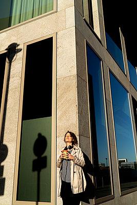 Junghe Frau sonnt sich an einer Hauswand in der Großstadt - p1212m1573536 von harry + lidy