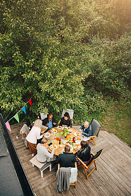 High angle view of senior woman serving friends sitting at dining table during garden party in back yard - p426m2194900 by Maskot