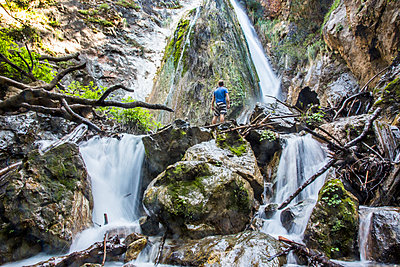 Caucasian man standing on rocks watching waterfall - p555m1482030 by Adam Hester