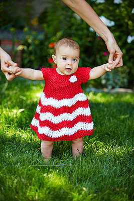 Baby Girl Taking First Steps in Garden - p669m1146518 by Kelly Davidson