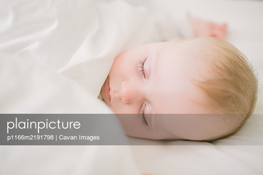 Peaceful and ethereal sleeping baby surrounded in white blanket - p1166m2191798 by Cavan Images