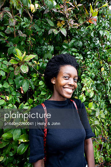 African woman in front of green leaves, portrait - p1640m2260041 by Holly & John