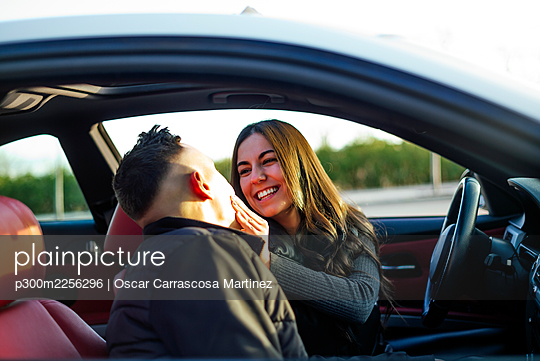 Girlfriend smiling while looking at boyfriend sitting in car - p300m2256296 by Oscar Carrascosa Martinez