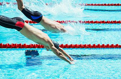 Swimmers diving into pool - p1023m923596f by Paul Bradbury