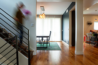 Blurred motion of woman moving down steps at home - p1166m1163606 by Cavan Images