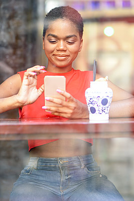 Portrait of smiling young woman in a bar looking at cell phone - p300m2131999 by Javier Sánchez Mingorance