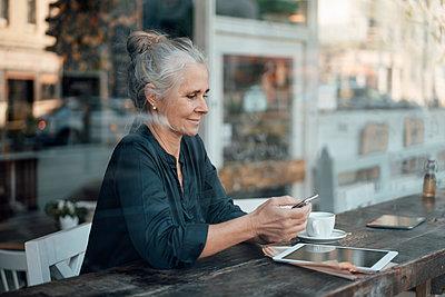 Female freelancer using mobile phone while sitting in cafe seen through glass window - p300m2299282 von Joseffson