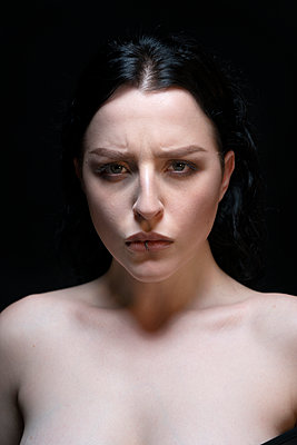 Portrait of frowning woman with lip piercing - p427m2181252 by Ralf Mohr
