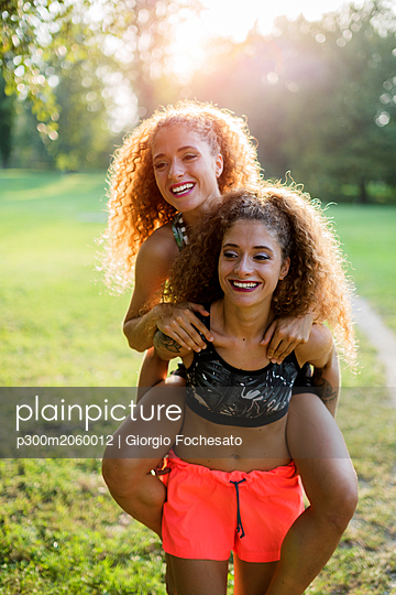 Portrait of happy young woman giving her laughing twin sister a piggyback ride - p300m2060012 by Giorgio Fochesato
