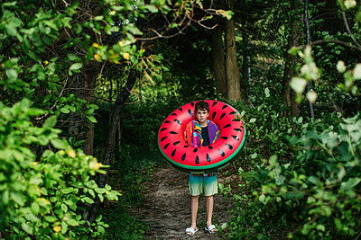 Teen boy with watermelon float ready for the beach - p1166m2157279 by Cavan Images