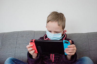 boy playing with a game console with a face mask on as protection - p1166m2171945 by Cavan Images