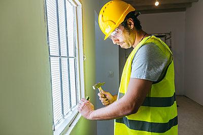 Worker with hammer working at the window - p300m1587283 by Kiko Jimenez