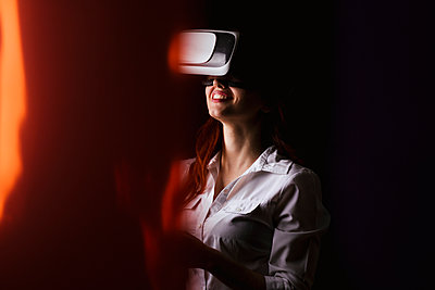 Young woman smiling while using VR glasses over black background - p300m2198545 by DREAMSTOCK1982