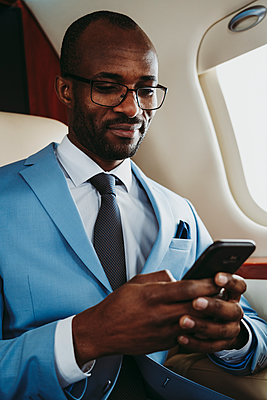 Smiling businessman text messaging on smart phone while traveling through airplane - p300m2256374 by OneInchPunch
