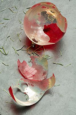 Rote, kaputte Weihnachtsbaumkugel zerbrochen am Boden. - p948m2014766 von Sibylle Pietrek