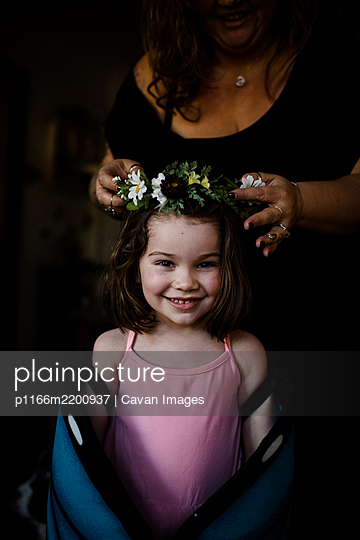 Aunt placing flower crown on niece's head - p1166m2200937 by Cavan Images