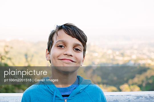 Smiling ten year old boy sands in front of a view overlook in LA - p1166m2201518 by Cavan Images