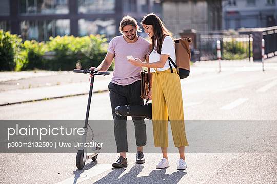 Young couple with electric scooter and smartphone on the street - p300m2132580 by Uwe Umstätter