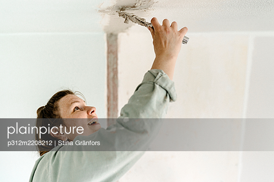 Woman putting cement on ceiling - p312m2208212 by Stina Gränfors
