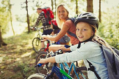Portrait mother and daughter mountain biking in woods - p1023m1402883 by Paul Bradbury