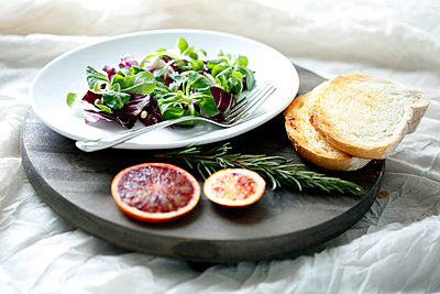 High angle view of salad with blood orange and rosemary by bread on cutting board - p1166m1561225 by Cavan Images