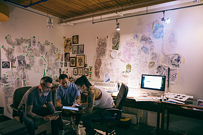 Tattoo artists brainstorming with digital tablet in tattoo studio office - p1192m1529775 by Hero Images