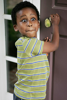 A boy with a surprised expression standing at the front door or his house - p301m714613f by Tamara Lackey