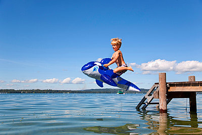 Boy jumping into lake with toy whale - p42916682f by Henglein and Steets
