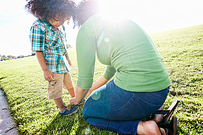 Mixed race mother tying shoe of son - p555m1523007 by Peathegee Inc
