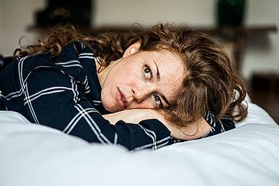Junge Frau auf dem Bett denkt nach - p586m1144018 von Kniel Synnatzschke