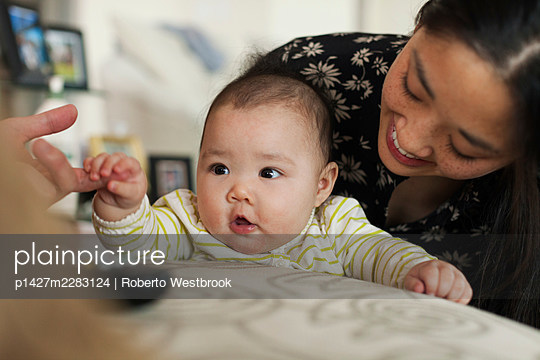 Close up of parents playing with baby daughter - p1427m2283124 by Roberto Westbrook