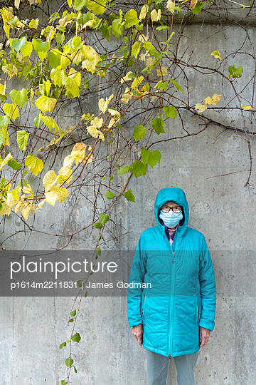 Woman in blue jacket and mask - p1614m2211831 by James Godman