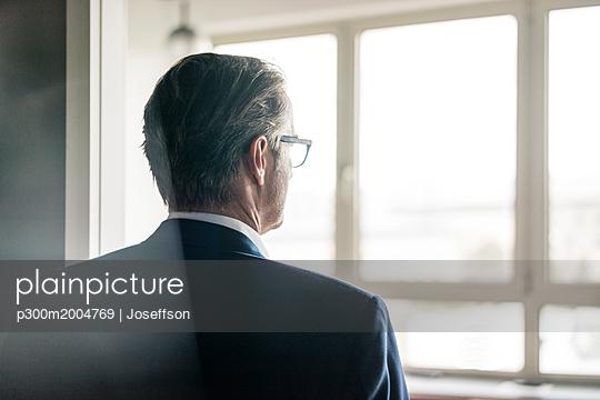 Rear view of mature businessman looking out of window - p300m2004769 von Joseffson