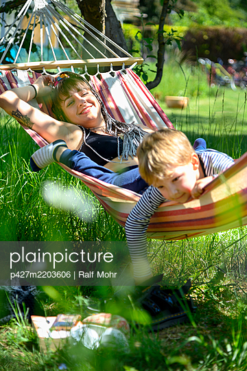 Young woman and toddler boy in a hammock - p427m2203606 by Ralf Mohr