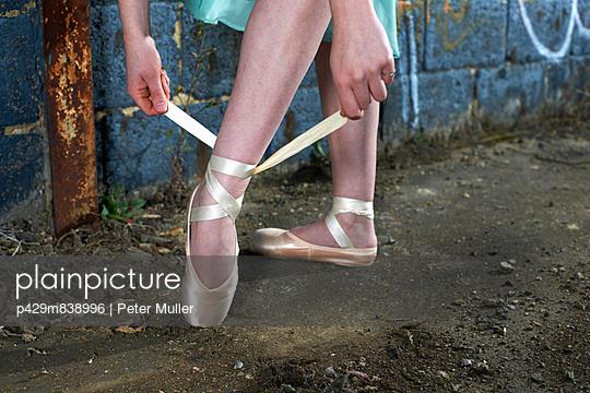 Ballet dancer tying ribbon on ballet shoe - p429m838996 by Peter Muller