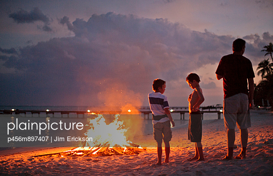 Man standing with to his two sons next to a camp fire on a sandy beach at dusk. - p456m897407 by Jim Erickson
