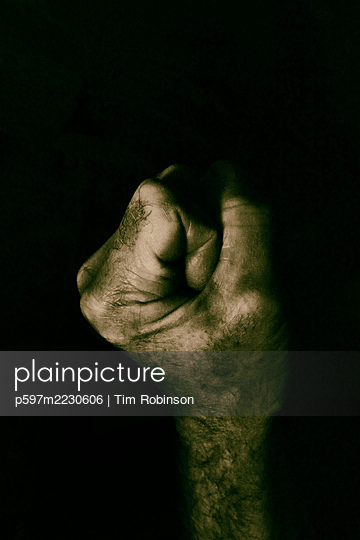 Clenched male hand in front of black background - p597m2230606 by Tim Robinson