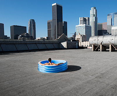 A man sitting in a small inflatable water pool on a city rooftop, cooling down.  - p1100m1107169 by Mint Images