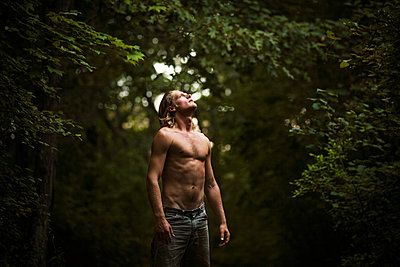 Shirtless man looking up while standing in forest - p1166m985479f by Cavan Images