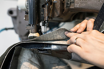 Cropped image of fashion designer sewing in jeans factory - p1185m994368f by Astrakan