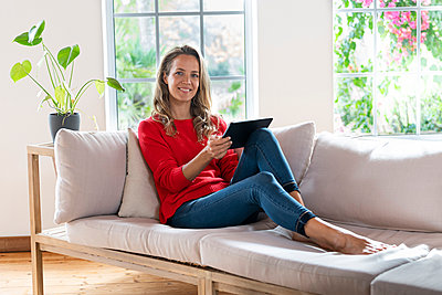Contented woman with digital tablet sitting on couch at home - p300m2276411 by Steve Brookland