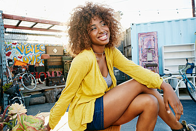 Smiling black woman sitting outdoors - p555m1521442 by Peathegee Inc
