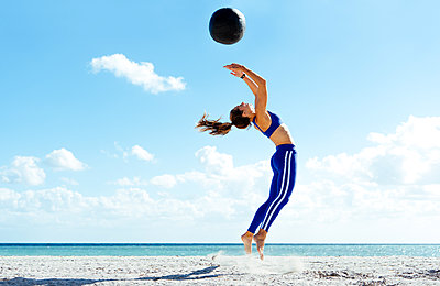 Young woman training, jumping mid air with exercise ball on beach - p924m1404226 by Corey Jenkins