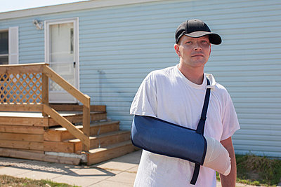 Man outside house with arm in sling - p924m711234f by Raphye Alexius