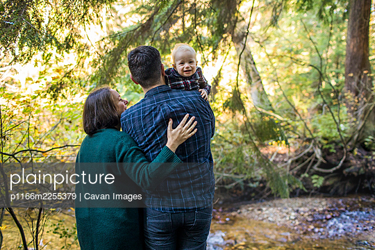 Young family, mother, father, son, outdoors near river. - p1166m2255379 by Cavan Images