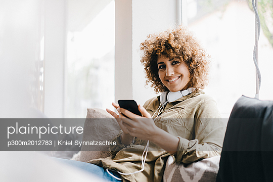 Young woman working in coworking space, using at smartphone - p300m2012783 von Kniel Synnatzschke